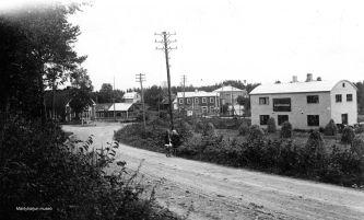 Asemankylää 1930-luvulla nykyisen sillan kohdalta. Vasemmalla postitalo, radan takana Laukkarisen kauppa, oikealla Kasurisen autokorjaamo. Kuva: Mäntyharjun museo.