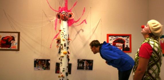 Leikkimielellä - kolmen sukupolven taidetta. Kuvan teos on leluja kahmiva mörkö. Elma-neiti valvoo näyttelyä. Näyttely ripustettiin lasten korkeudelle, jotan aikuiset joutuivat vähän kumartumaan.